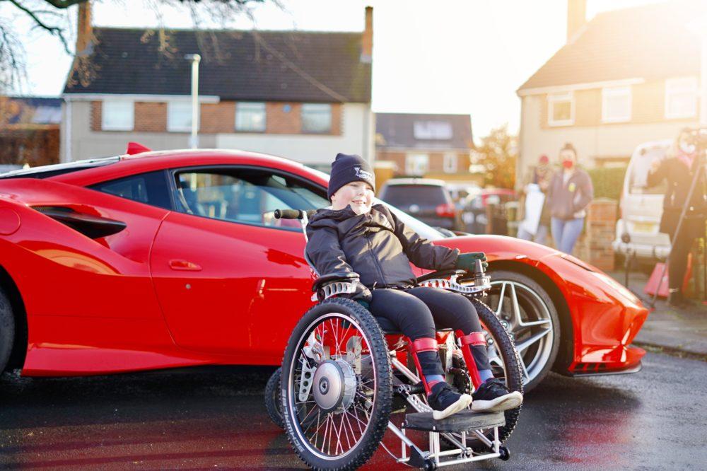 man in wheelchir next to a supercar
